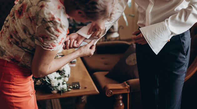 Mother Helping Son With Cuff Links For His Wedding Day