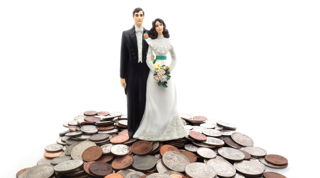 plastic bride and groom standing on mountain of money coin