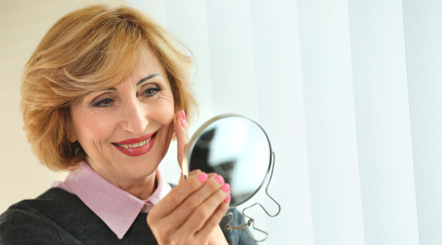 made up senior woman looking in handheld mirror
