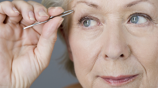 mature woman tweezing eyebrows