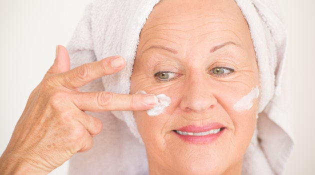 senior woman applying face moisturiser